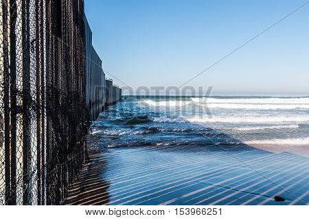 Close-up view of the international border wall extending out into the ocean between San Diego, California and Tijuana, Mexico at Border Field State Park.