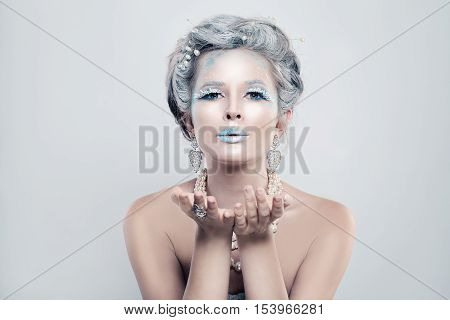 Winter Woman Fashion Model with Snow Glitters Makeup Blowing a Kiss