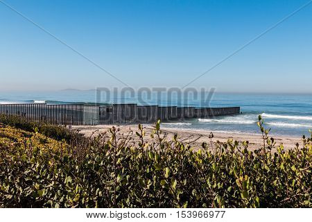 Border Field State Park beach with the international border wall separating Tijuana, Mexico from San Diego, California and the Islas Los Coronados islands in the background.