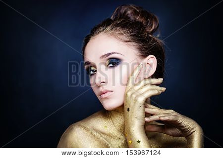 Magnificent Woman with Golden Hands on Blue Background
