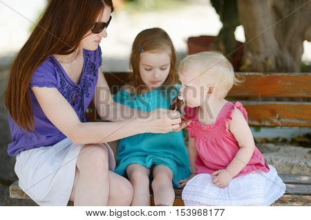 Young mother and her daugthters eating ice cream outdoors