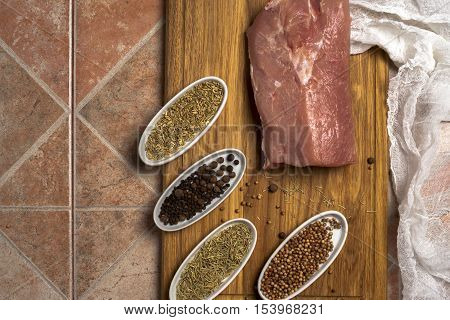 Fresh meat selection on wooden cutting board with spices in a white bowl.