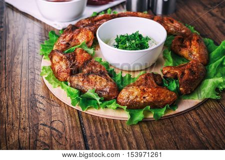 delicious grilled chicken wings with garlic and tomato sauce with lettuce on a round board on wooden rustic background.