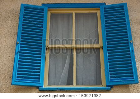 Blue  casement, yellow framed windows of an old but well-kept house