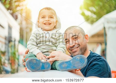 Portrait of a happy father for son's birthday party outdoor - Cheerful parent hugging his child in park with back lighting - Love and family concept - Warm vintage filter - Main focus on child