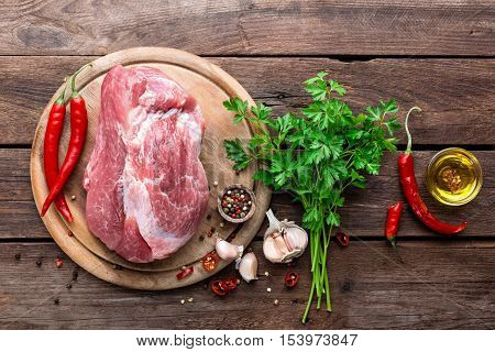 raw meat on wooden cutting board with ingredients