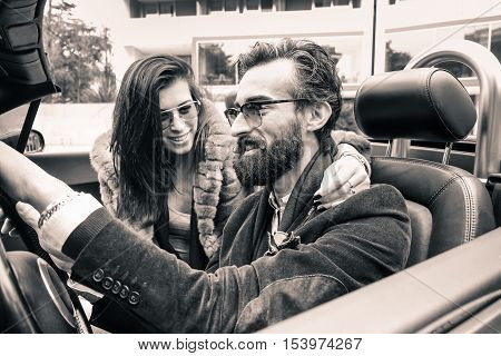 Hipster fashion couple ready for a road trip with a cabriolet roadster car - Young cheerful people smiling and having fun - Happiness and trendy concept - Black and white editing - Soft brown filter