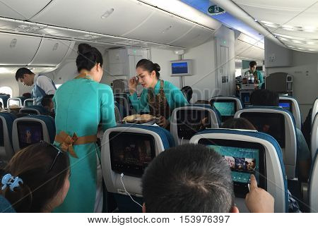 Ho Chi Minh, Vietnam - Dec 14, 2015: Vietnamese stewardess of Vietnam Airlines carrier serving fast food for lunch on a commercial flight from Hanoi capital to Ho Chi Minh City.