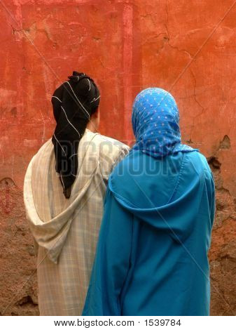morrocan colored muslim women in veil in front of a wall poster