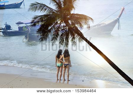 Travelers  girls swimsuit  Ao Nang  beach  Krabi ,The famous beach in Thailand . sunset at the beach .