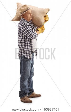 Full length profile shot of a mature farmer posing with a burlap sack on his shoulder isolated on white background