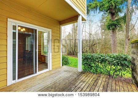 Empty Wooden Walkout Deck, Backyard View Of Yellow House