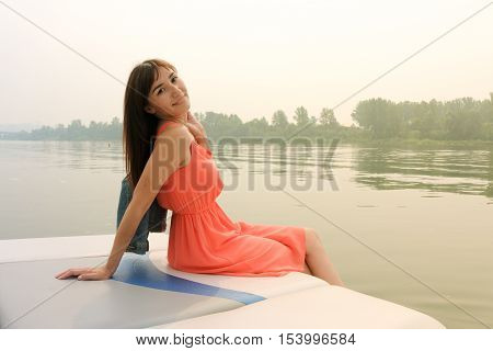 A woman in a pink dress sits on the stern of the yacht.