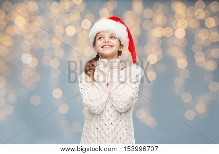christmas, people, children and holidays concept - dreaming girl in santa helper hat over lights background