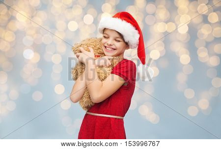christmas, people, holidays and childhood concept - smiling girl in santa helper hat hugging teddy bear over lights background