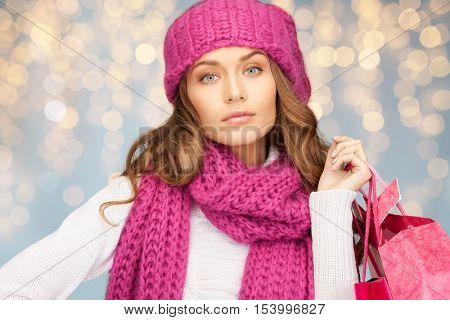 holidays, christmas, sale and people concept - happy young woman in winter clothes with shopping bags over lights background