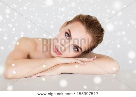 beauty, people, winter and bodycare concept - beautiful young woman face and hands over gray background and snow