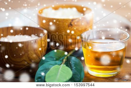 beauty, spa, bodycare, natural cosmetics and wellness concept - close up of honey in glass with leaves on wood over snow