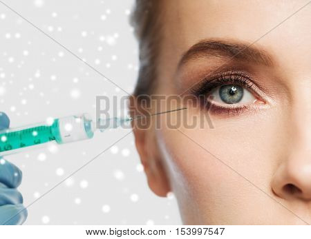 people, cosmetology, plastic surgery and beauty concept - close up of beautiful young woman face and beautician hand in glove with syringe making injection over gray background and snow