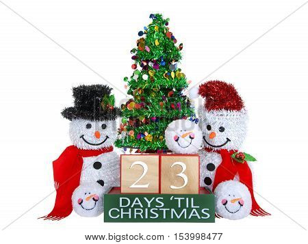 23 Days until Christmas light beech wood blocks with red trim on a green base with tinsel christmas tree mr and mrs snowman and snowball snowmen heads isolated on a white background.