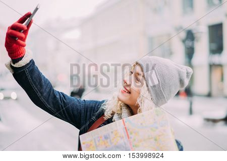 Young blond curly female tourist in warm clothes and red gloves with London map making selfie winter city