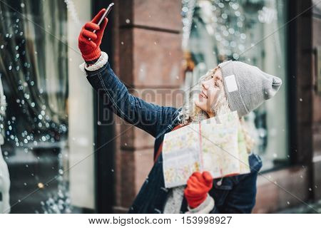 Young blond curly female tourist in warm clothes and red gloves with London map making selfie winter city blurred facade on background