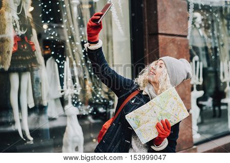Young blond curly female tourist in warm clothes and red gloves with London map smiling and making selfie winter city blurred facade on the background