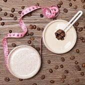 Cellulite busting cosmetic products concept. Anti-cellulite cosmetics with caffeine. Jar of cream with coffee essential oil, natural body scrub, body measuring tape and scattered coffee beans poster