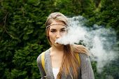 Happy vaping young white blonde girl.Smiling female model smoking fruit flavored e-liquid or e-juice with vaporizer device or e-cig.Modern gadget for smokers poster