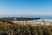 Border Field State Park beach with the international border wall separating Tijuana, Mexico from San Diego, California and the Islas Los Coronados islands in the background. poster