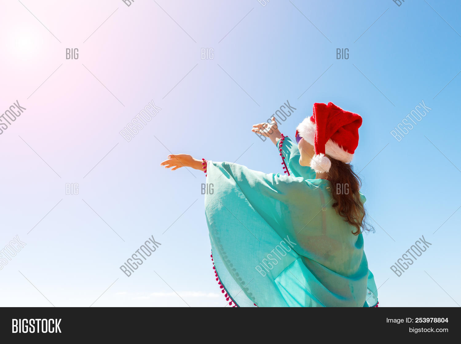 8fc705ba732 Woman with hands outstretched to the sky on the beach. Rear view of a  tourist in a santa hat and bikini enjoying the Christmas holidays on a  sunny day. copy ...