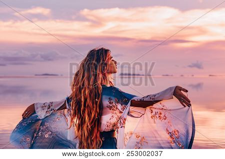 Beautiful Young Woman In Elegant Dress On The Beach At Sunset