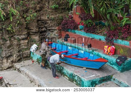 Two Workers Are Painting A Wooden Boat On April 11, 2018 In Pokhara, Nepal.