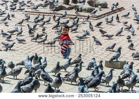 The Boy Stands In The Square Among A Large Flock Of Pigeons On 13 April 2018 In Kathmandu, Nepal.
