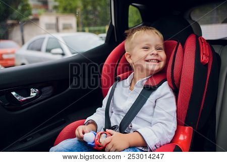 Baby Boy With Curly Hair Sitting In Child Car Seat With Toy Car In Hands