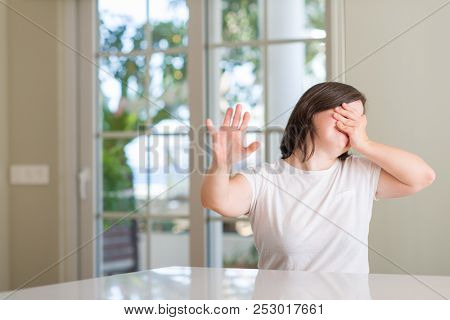 Down syndrome woman at home covering eyes with hands and doing stop gesture with sad and fear expression. Embarrassed and negative concept. poster