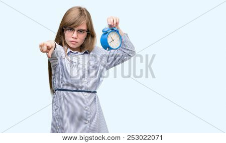 Young blonde child holding alarm clock pointing with finger to the camera and to you, hand sign, positive and confident gesture from the front