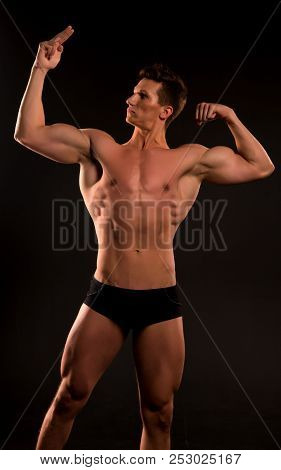 Muscular Man. Muscular Man With Abs. Muscular Man Bodybuilder Point On His Muscle. Biceps And Tricep