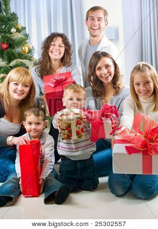 Happy Big family holding Christmas presents at home.Christmas tree