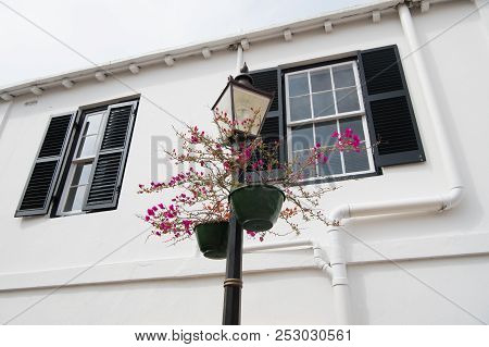 Street Lamp With Flower Pots On House Facade In Hamilton, Bermuda. Potted Flowers On Lighting Column