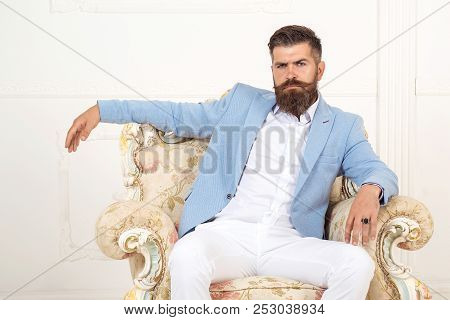 Successful Young Bearded Elegant Businessman In Suit With Perfect Hairstyle Indoors, Relaxing, Sits