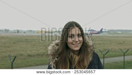 Woman looking at camera and smiling. Airport and airplane in background.