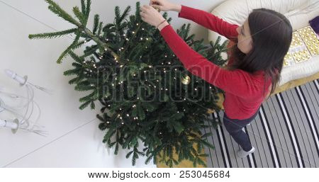 Woman in red sweater decorating the Christmas tree. Stedy schoot from above.
