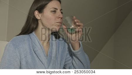 Casual young woman washing her mouth with antiseptic liquid.