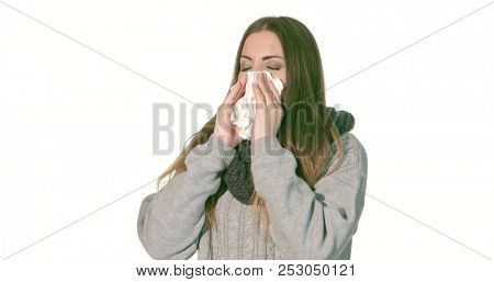 Young ill woman sneezing against white background.