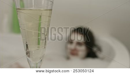 Portrait of woman in bathtub with clay mask on face drinking champagne.