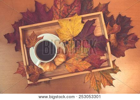 Cup Of Coffee, Croissants And Autumn Maple Leaves On Wooden Table