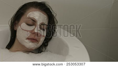 Portrait of a woman in facial mask lying in the bath in the bathroom. Home relax and resting concept.