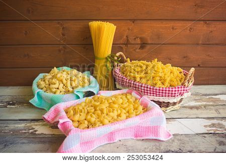 Different Kinds Of Raw Pasta On Wooden Table