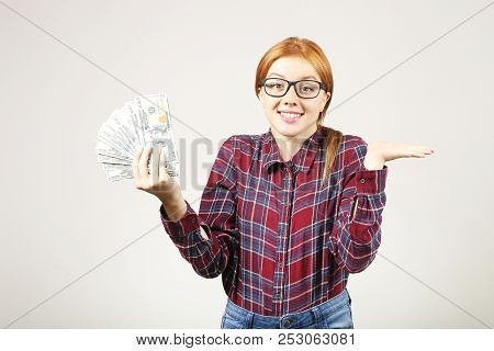 Portrait Of Young Beautiful Redhead Woman With Fistful Of One Hundred Dollar Bill Stack, Holding Lik